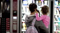 Mother and daughter selecting a snacks at vending machine inside airport video