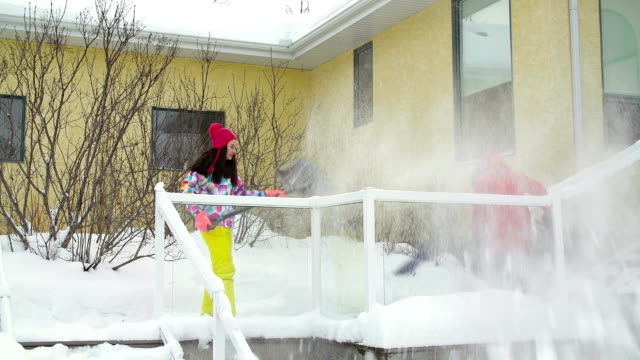 Mother and daughter shoveling snow off house deck and steps video
