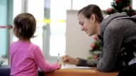 Mother and daughter sitting in waiting hall at airport with exercise book video