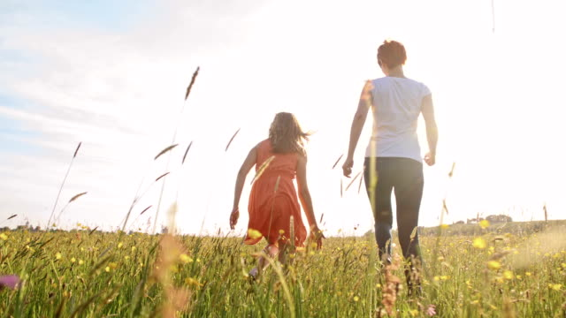 SLO MO Mother and daughter skipping in the meadow video