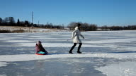 Mother and daughter sledding on frozen lake video