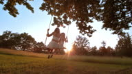 SLO MO Mother and daughter swinging at sunset video