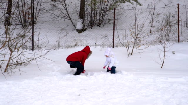 Mother and daughter throw up soft, fresh snow. Woman and a girl child is rejoice winter. A cloudy winter day in the park. Slow motion. video