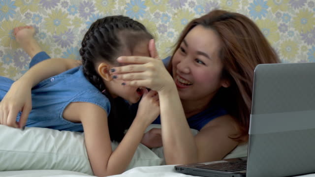 Mother and daughter using laptop video