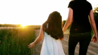 Mother and Daughter Walking at Sunset Through Tall Grass video