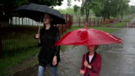 Mother and daughter walking on the street in heavy rain. video