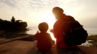 Mother and daughter watching sunset. video
