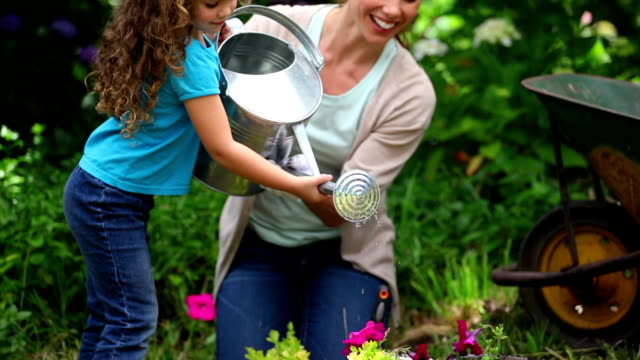 Mother and daughter watering flowers together video