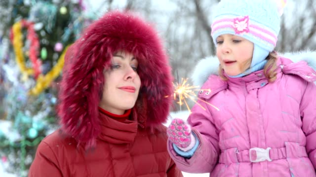Mother and daughter with sparkler against christmas tree video