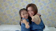 Mother and daughter with thumbs up video