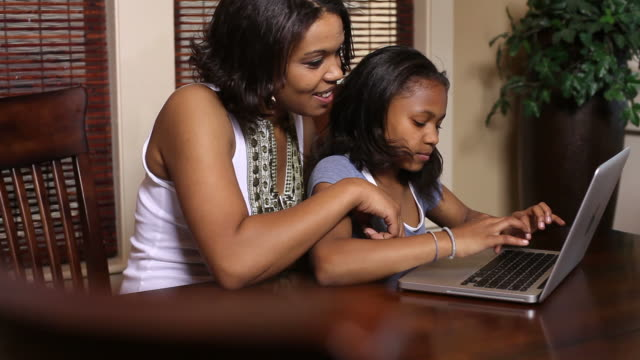 Mother and daughter working on laptop video
