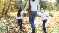Mother and daughters run in fall leaves, slow motion video