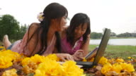 mother and daugther lying on grass and work with laptop video