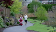 Mother and father exercising with their new baby in a stroller video