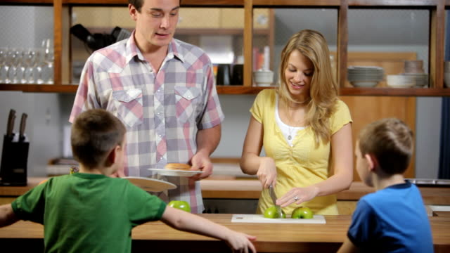 Mother and Father in kitchen prepare snack for kids video