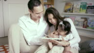 Mother and Father reading with their baby in bedroom video