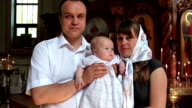 Mother and father with baby in orthodox church after christening ceremony video