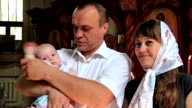 Mother and father with baby in orthodox church video