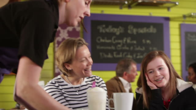 Mother and father with daughter in cafe video
