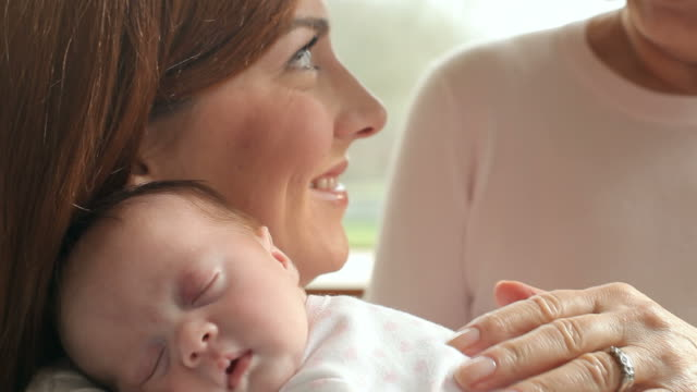 Mother And Grandmother With Sleeping Newborn Baby Daughter video