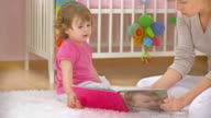 HD DOLLY: Mother And Her Baby Looking A Book video