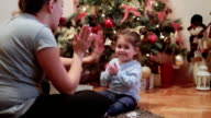 mother and her baby playing clapping games and hugging under the christmas tree video
