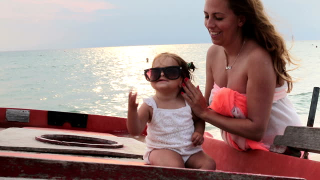 mother and her daughter , baby girl , enjoying on a boat near the sea video