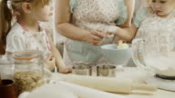 Mother and Her Little Daughters Preparing Cookies in the Kitchen video