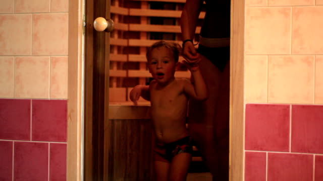 Mother and her son leaving sauna. video