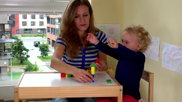 Mother and her toddler girl playing with wooden bricks toys on small table video