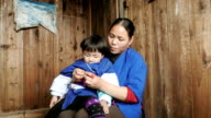 Mother and her young child on her lap in China video