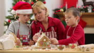 Mother and kids decorate Gingerbread house for Christmas video