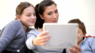 Mother and kids taking selfie with tablet computer video