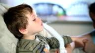 Mother and little boy inhaling medicine using nebulizer video