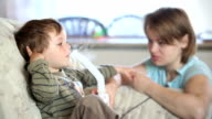 Mother and little boy using nebulizer to inhale medicine video