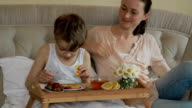 Mother and son having breakfast in bed video