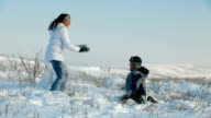 Mother and son having snowball fight video