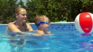 Mother and son in swimming pool. Son learning to swim video