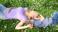 Mother and son laying in grass, laughing. video