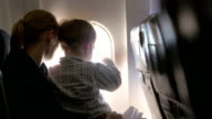 Mother and son looking out illuminator in plane video