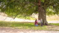 Mother and son paint the colorful pictures under a tree near the forest video