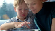 Mother and son playing game on pad in train video