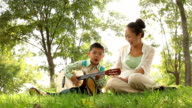 mother and son playing guitar in the park video