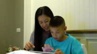 Mother and son playing on a digital tablet together video