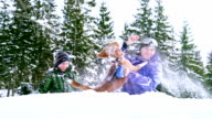 Mother and son playing with beagle dog in deep snow video