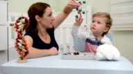 DOLLY: Mother and son playing with model molecular structures video