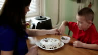 Mother and son putting chocolate on the top of a cake. video