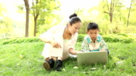 mother and son resting outdoor with laptop video