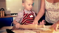 Mother and son rolling the dough for cake using rolling pin video
