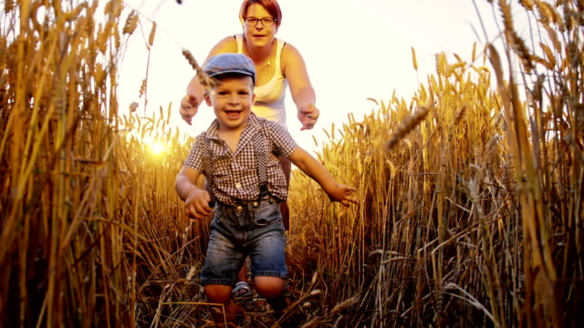 SLO MO Mother and son running in field of wheat video